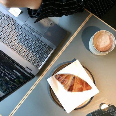 Mand som arbejder på sin bærbær computer ved bordet med en croissant og kaffe ved siden af